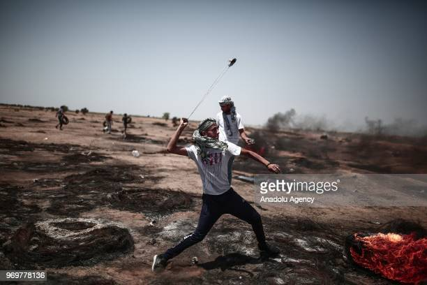 Palestinians use slingshot to throw stones during the protests called commemorating the Naksa along the border fence east of Khan Yunis in the...