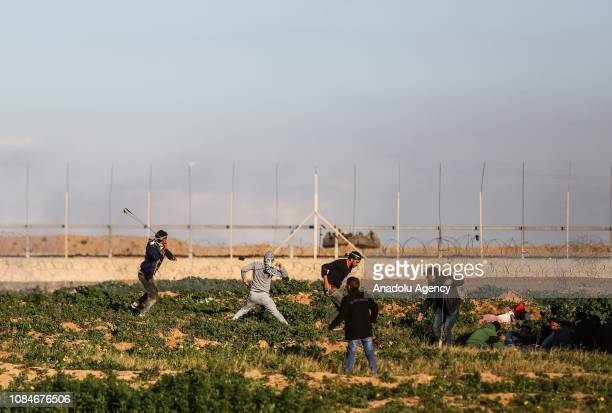 Palestinians use slingshots to throw stones after Israeli forces' intervention during a protest within 'Great March of Return' demonstrations in Khan...