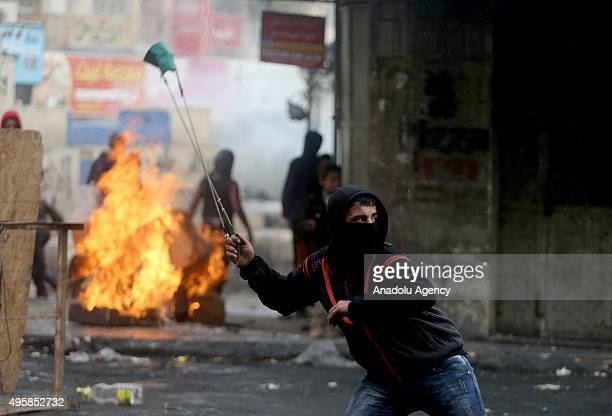Palestinians uses a slingshot to throw stones to respond Israeli soldiers' intervention during a protest against Israeli violations in Hebron West...