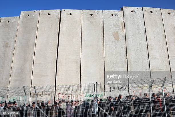 Line of people at tall wall in Palestine