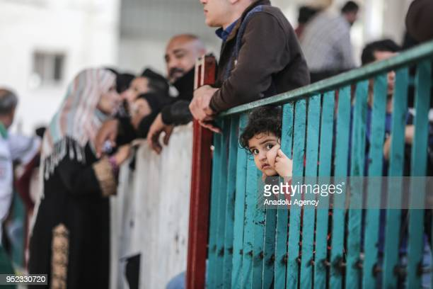 Palestinians wait in line for passport transactions to cross to Egypt following the opening of Rafah border gate in Khan Yunis, Gaza on April 28,...