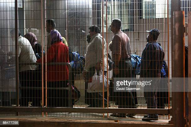 Palestinians wait in line to undergo a security check as they cross from the West Bank town of Qalqilya to work in the Jewish state at the Israeli...