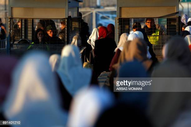 Palestinians wait to cross the Qalandia checkpoint between the West Bank city of Ramallah and Jerusalem as they head to Jerusalem's AlAqsa Mosque...