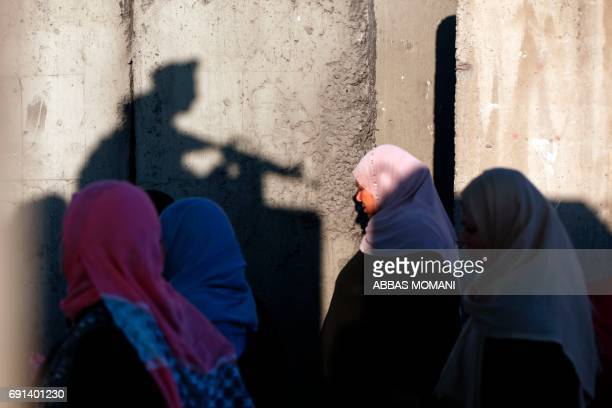 TOPSHOT Palestinians wait to cross the Qalandia checkpoint between the West Bank city of Ramallah and Jerusalem as they head to Jerusalem's AlAqsa...