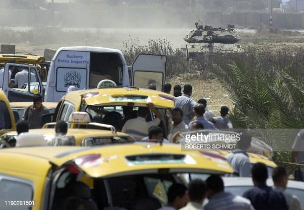Palestinians wait to cross the Saladin highway the main northsouth road which runs the entire length of the Gaza Strip while looking at an Israeli...