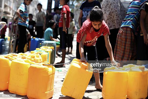 Palestinians wait to fill plastic bottles and water containers with drinking water from a public tap in the Shati refugee camp west of Gaza City at...