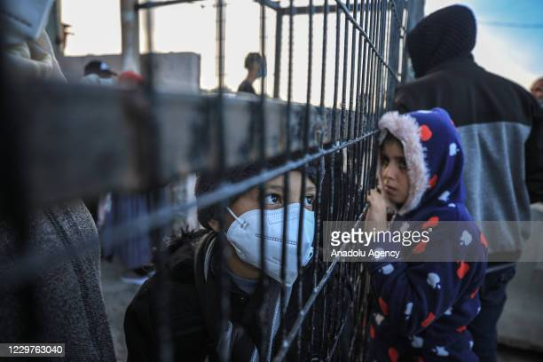 Palestinians wait with their luggage to cross the border after Egypt exceptionally opened the Rafah border crossing with the Gaza Strip for three...