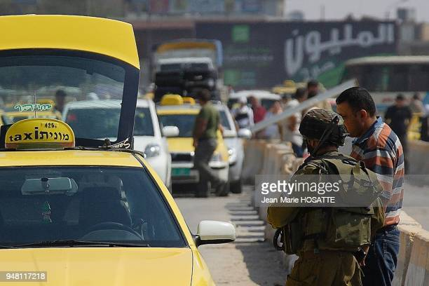 Palestinians walk across the hawara Israeli military checkpoint near Nablus West Bank on August 08 2007