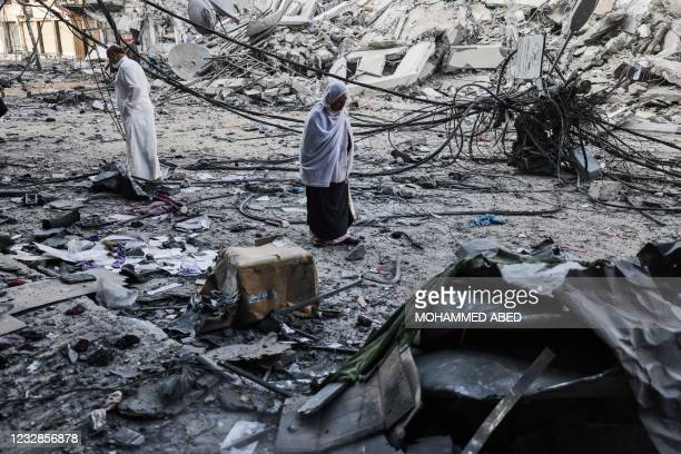 Palestinians walk after performing Eid al-Fitr prayers amidst debris near the al-Sharouk tower, which housed the bureau of the Al-Aqsa television...