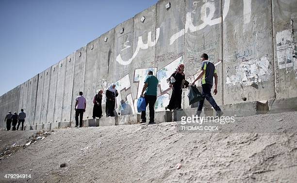 Palestinians walk along the separation wall barrier at the Israeli army check point of Qalandia between the West Bank city of Ramallah and Jerusalem...
