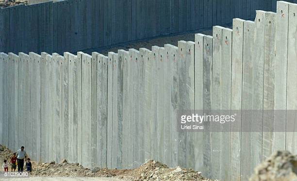 Palestinians walk alongside Israel's separation barrier on July 9 2004 where the 9meterhigh concrete wall cuts the West Bank Palestinian village of...
