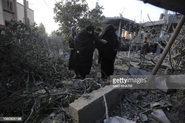 TOPSHOT Palestinians walk amidst rubble of a residential building that was destroyed in an Israeli air strike in Khan Yunis in the southern Gaza...