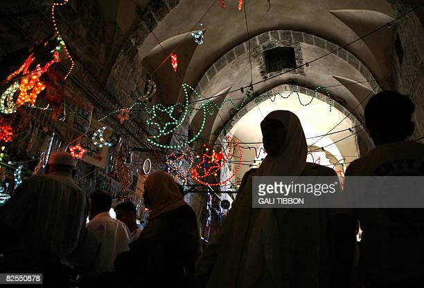 Palestinians walk beneath decorative lights hanged for the upcoming Muslim holy month of Ramadan on August 26 2008 at the Muslim Quarter in...