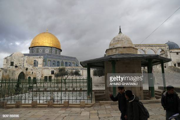 Palestinians walk near the Dome of the Rock in Jerusalem's Old City in alAqsa mosque compound on January 23 2018 / AFP PHOTO / AHMAD GHARABLI