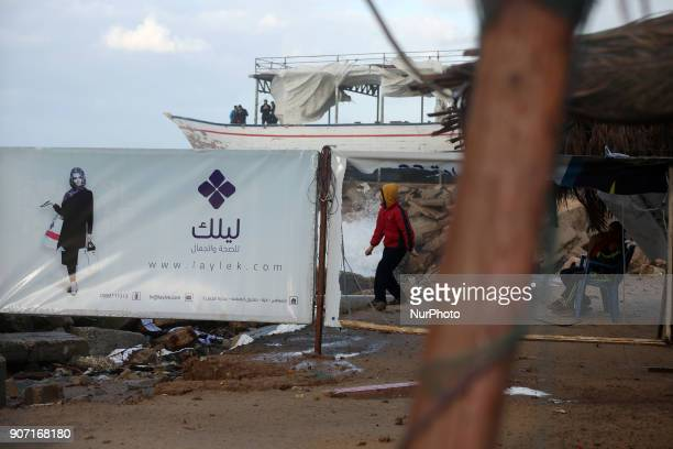Palestinians walk next to coffee shop damaged by strong winds during a storm in Gaza City on January 19 2018