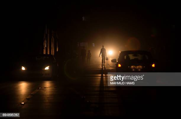 Palestinians walk on a street at the AlShati refugee camp in Gaza City during a power outage on June 11 2017 Hamas this week marks 10 years since...