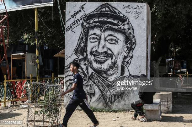 Palestinians walk past a graffiti depicting late Palestinian leader Yasser Arafat in Rafah in the southern Gaza Strip on November 11 on the 16th...