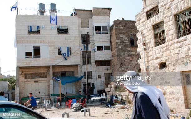Palestinians walk past a house occupied by a group of Israeli settlers the previous day in the divided West Bank town of Hebron on July 26, 2017....