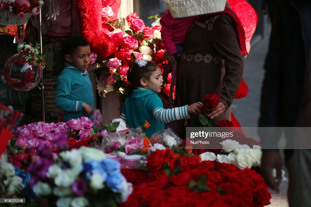 Palestinians walk past a shop selling red teddy bears, red balloons and pillows on Valentine's day in Gaza city on February 14, 2018.