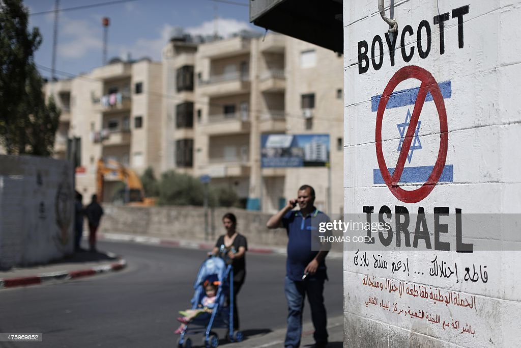 Palestinians walk past a sign painted on a wall in the West Bank biblical town of Bethlehem on June 5, 2015, calling to boycott Israeli products coming from Jewish settlements. The international BDS (boycott, divestment and sanctions) campaign, that pushes for a ban on Israeli products, aims to exert political and economic pressure over Israel's occupation of the Palestinian territories in a bid to repeat the success of the campaign which ended apartheid in South Africa.
