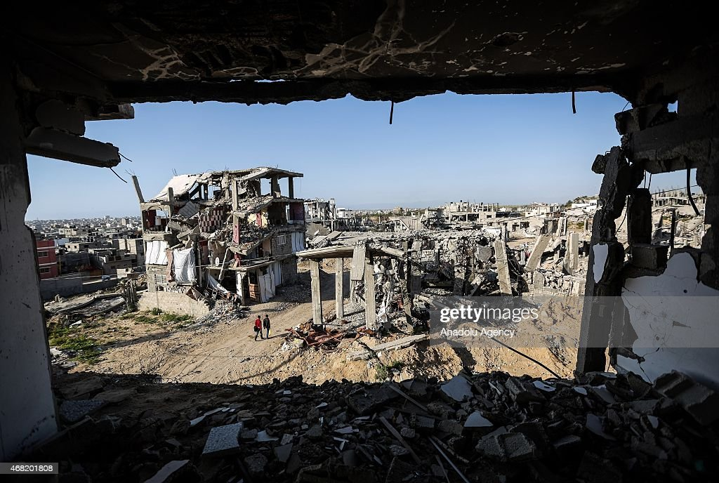 Palestinians walk past buildings which were destroyed in the 51-day Israeli military onslaught, in Shujaiya district of Gaza City on March 31, 2015.