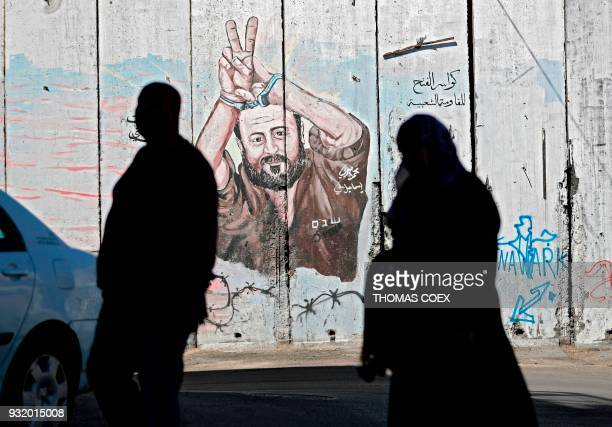 Palestinians walk past graffiti depicting Palestinian prisoner Marwan Barghuti on Israel's controversial separation barrier in the West Bank city of...