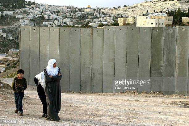 Palestinians walk past Israel's controversial security wall in Abu Dis separating it from Jerusalem 02 January 2004 In the background is the Dome of...