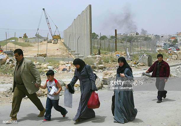 Palestinians walk past Israel's security wall under construction May 6, 2004 through the Qalandia checkpoint on the outskirts of the West Bank...