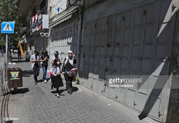 Palestinians walk past shuttered Palestinian stores in the city of Ramallah, as a general strike is observed in the occupied West Bank and Arab...
