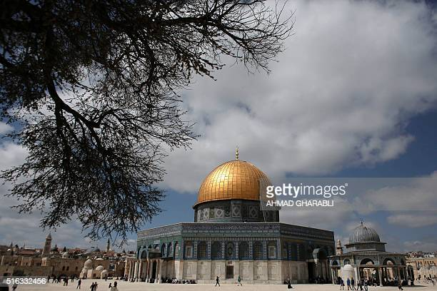 Palestinians walk past the Dome of the Rock at the AlAqsa Mosque compound in Jerusalem on March 18 2016 / AFP / AHMAD GHARABLI