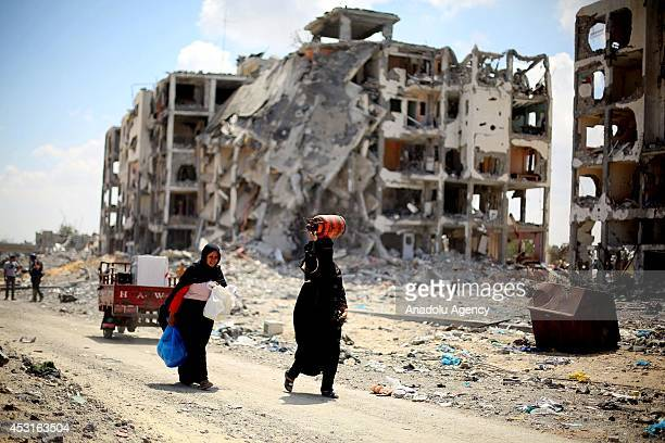Palestinians walk through the ruins of their buildings during a ceasefire which starts at 10 o'clock in the morning in Beit Lahia Gaza on August 04...