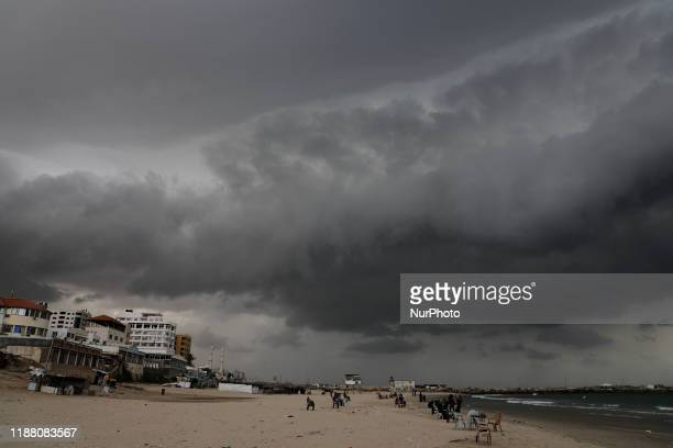 Palestinians walking on a beach along the Mediterranean Sea during a sandstorm in Gaza City on December 12 2019