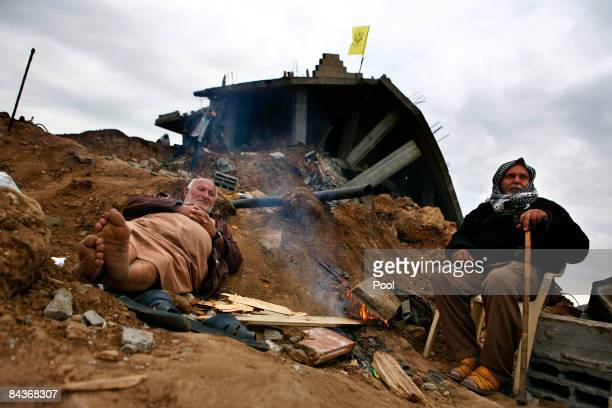 Palestinians warm themselves by a fire near the ruins of a destroyed house on January 20, 2009 on the outskirts of Jabalya, Gaza Strip. Israeli plans...