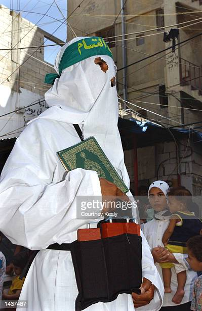 Palestinians watch a Hamas supporter dressed as a suicide bomber as he marches in a Hamas demonstration while carrying a Koran in Ain El Helweh...