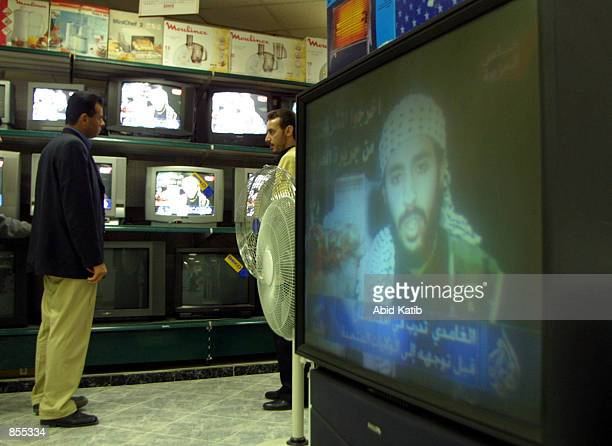 Palestinians watch AlJazeera television as it shows the videotaped will of one of the men who carried out the September 11th attacks pledging to die...