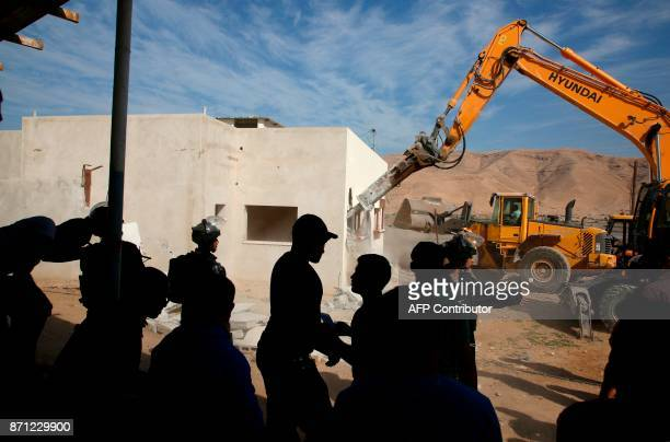 Palestinians watch as an Israeli army bulldozer demolishes a Palestinian house that was reportedly built without permission in the West Bank village...