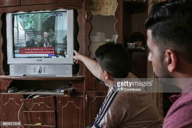 TOPSHOT Palestinians watch on TV the signing of a reconciliation deal in Cairo between rival Palestinian factions Hamas and Fatah on October 12 in...