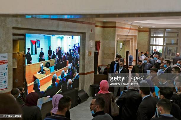 Palestinians watch proceedings on a giant screen as a judge opens the first session in a lawsuit filed by activists seeking compensation from Britain...
