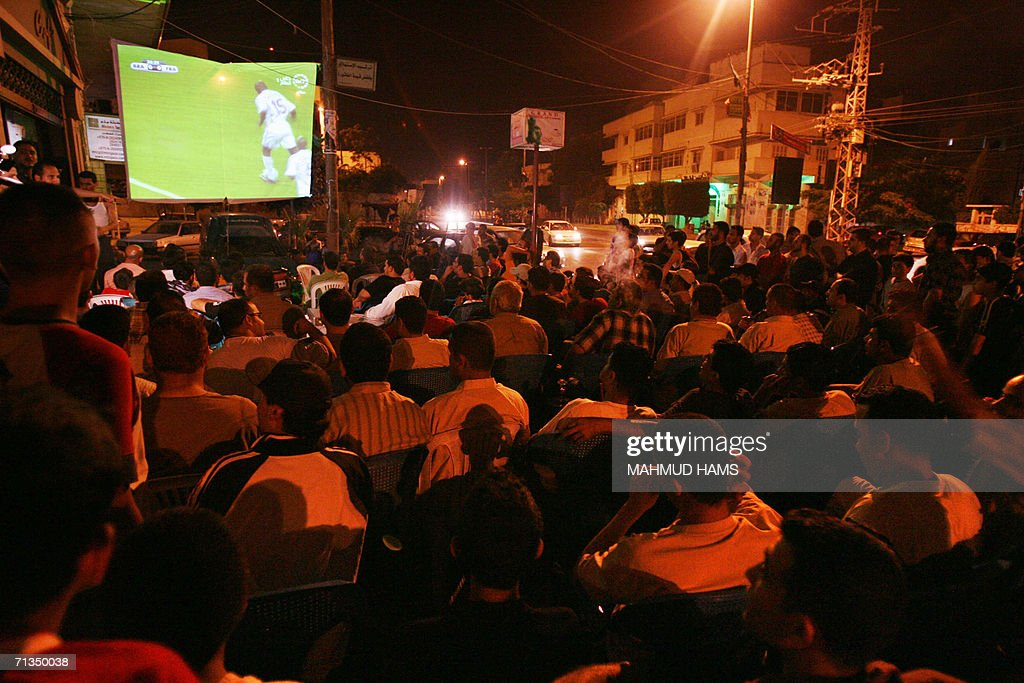 Palestinians watch the World Cup 2006 quarter final match between Brazil and France on a giant retransmission screen near a coffee shop in Gaza City 01 July 2006. Palestinian officials organised the distraction as the Israeli offensive in the Gaza strip continued, following the capture of an Israeli soldier in June. A United Nations official said Saturday that food stocks in Gaza were now running out or impossible to distribute because of the blockade and interdiction of routes.