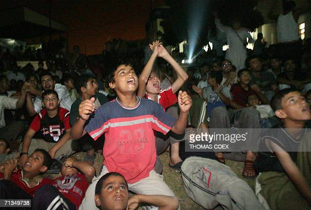 Palestinians watching the 2006 World Cup football match Brazil against France on a giant screen in the stadium of Rafah in the Gaza Stripe jubilate...