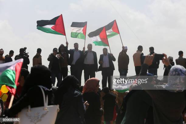 Palestinians wave flags along Israel border with Gaza ahead of a protest in a tent city demanding to return to their home land east of Gaza City...