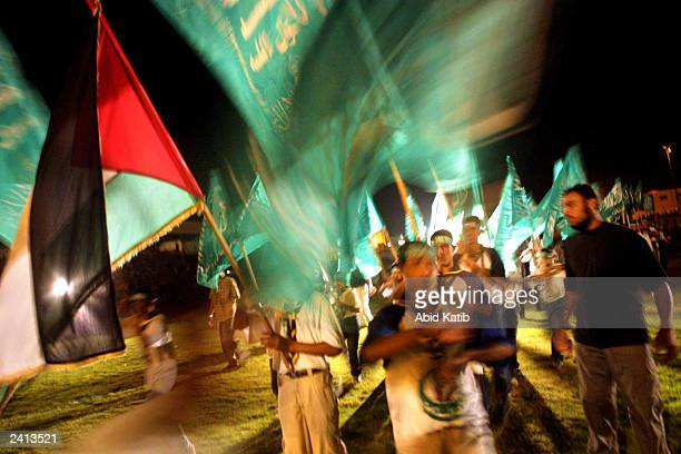 Palestinians wave national and Islamic flags as they celebrate during a mass wedding in the Youths stadium August 20, 2003 in Rafah refugee camp,...
