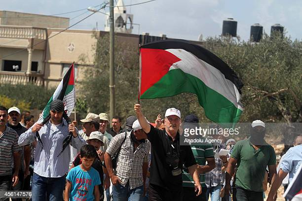 Palestinians wave national flags as they march during a protest against the expropriation of Palestinian land by Israel and the Israeli Wall of...