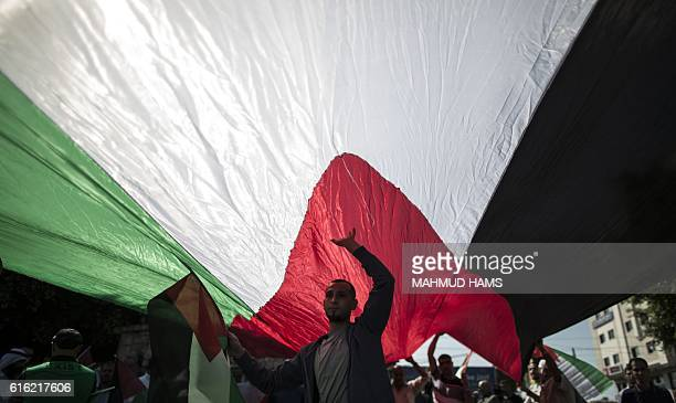 TOPSHOT Palestinians wave Palestinian flags during a demonstration against the division and in support with the national unity on October 22 2016 in...