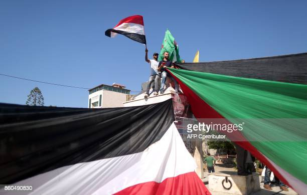 TOPSHOT Palestinians wave the flags of Egypt and Palestine as they gather in Gaza City to celebrate after rival Palestinian factions Hamas and Fatah...