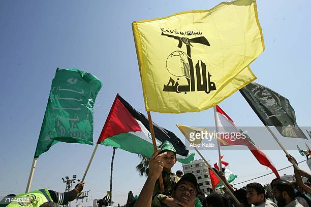 Palestinians wave the Lebanese Hezbollah Hamas flags in the courtyard of the Palestinian parliament July 14 in Gaza City Gaza Strip Hundreds attended...