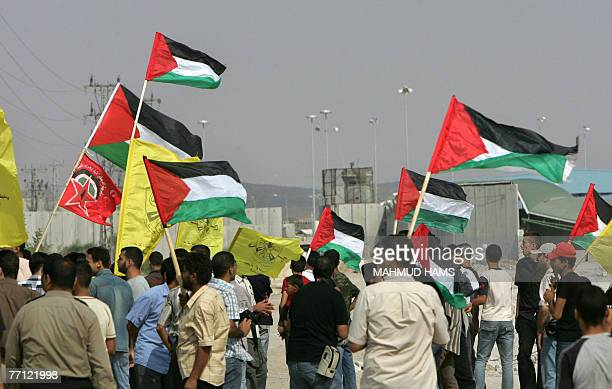 Palestinians wave their country's flag as they wait for relatives released from Israeli prisons at the Erez crossing northern Gaza Strip 01 October...
