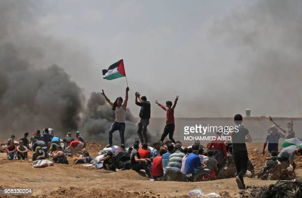 TOPSHOT Palestinians wave their national flag as they demonstrate near the border between Israel and the Gaza Strip east of Jabalia against the...