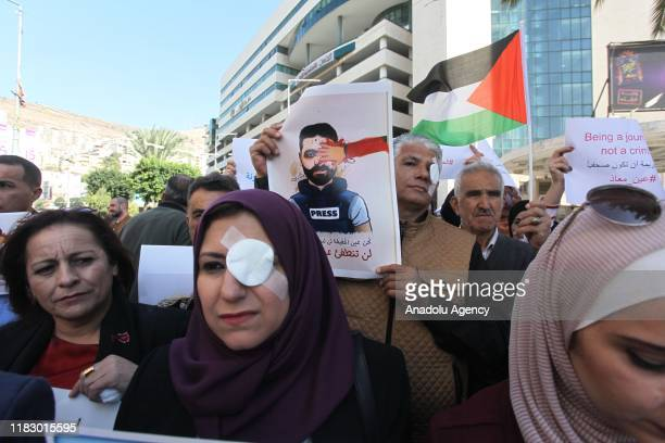 Palestinians wearing left eye patch gather to stage a demonstration to protest against Israeli oppressions and violations towards journalists in...