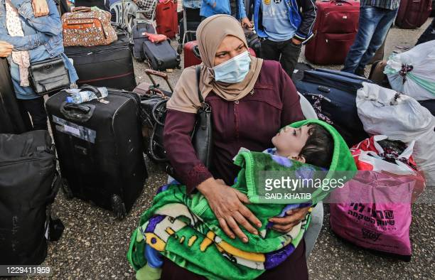Palestinians, wearing protective face masks due to the COVID-19 pandemic, wait their turn to cross into Egypt through the Rafah border crossing from...